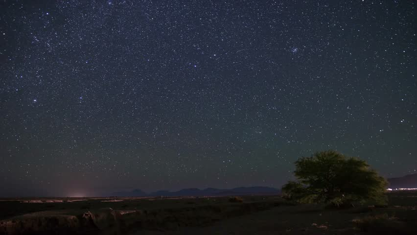 Night Timelapse of the Stars in the Atacama Desert in Northern Chile with views of Sirius - the brightest star - and city lights from San Pedro de Atacama. Tree, car lights, green glow