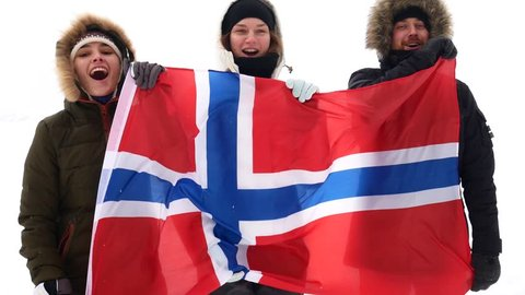 Norwegian fans with the national flag scream and jump.