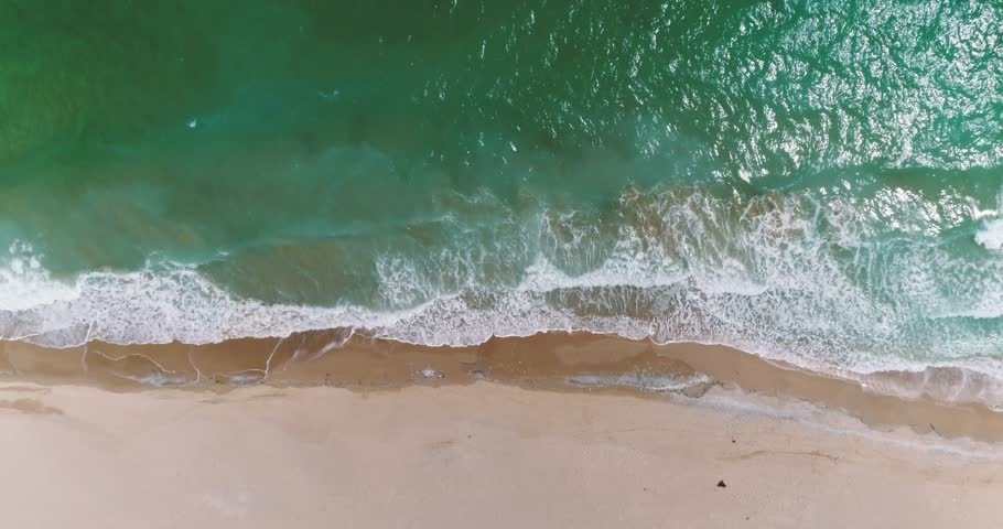 Aerial drone footage of waves reaching shore. Beach on top view.   | Shutterstock HD Video #1007031538