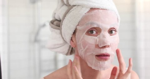 Woman applying cosmetic Japanese mask on her face and looking in the mirror looking at camera in the bathroom