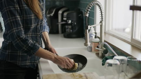 Woman washing pan talking on cell phone and dropping it into sink / Alpine, Utah, United States