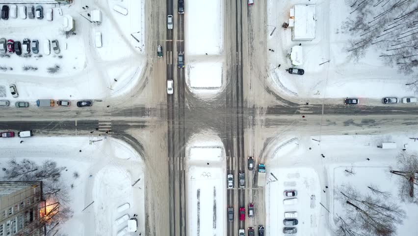 City streets crossing at winter season, top-down aerial perspective. Common auto traffic on roads, snow lie around. Lanes of larger avenue divided with white lawn. Vehicles move straight across square