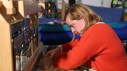 Young woman with down syndrome weaving loom 1/5