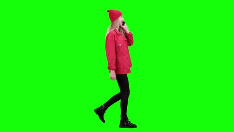 Teenage stylish girl is walking down the street and talking on the phone. Green screen. Side view
