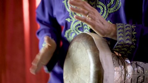 Closeup of a female Arabic percussionist playing the rhythm beladi on a decorated clay doumbek with fish skin head.