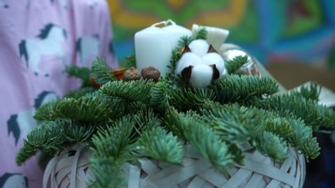 Girl in pink dress holds a handcrafted christmas table centerpiece arrangement: a basket with fir-tree branches, faux berries, cotton balls, candles and ribbons, close-up.