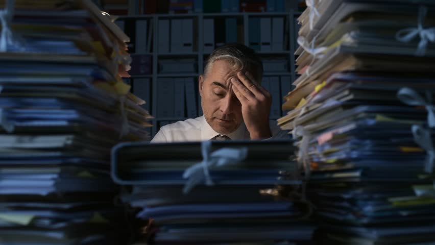 Tired businessman working late at night, he is overwhelmed by work and his desk is filled with paperwork, work overtime and deadlines concept | Shutterstock HD Video #1007116468