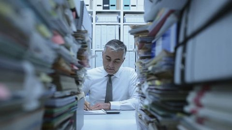 Business executive overwhelmed by work, he has piles of paperwork and files on his desk