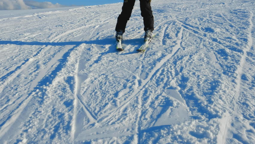 Skier having fun on snow mountain. Legs view of young man on ski slope. Winter sport, travel and vacation concept. Boy feet skiing downhill. Recreation, leisure outdoor activities. Alpine ski resort.