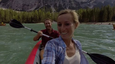 Young couple canoeing on lake Braies, Italy, taking selfies point of view. Couple taking selfies on a canoe surrounded by stunning mountain lake. Couple canoeing point of view selfie