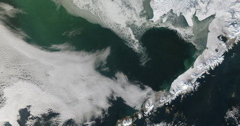 Very high-altitude overflight aerial of a frozen Bering Sea and west coast of Alaska. Clip loops and is reversible. Elements of this image furnished by NASA