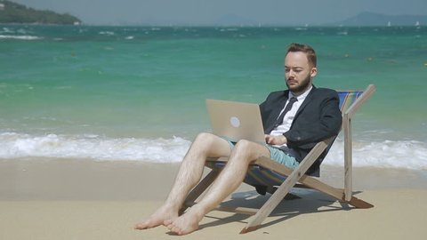 Young businessman is doing work using laptop while sitting on seashore. Bearded man is in work ing process, in deck chair on picturesque shore. Handsome guy in suit with tie has good time on beautiful beach