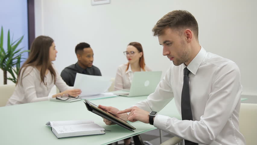 The businessman prepares for the presentation in co-working room with his colleagues. The handsome man in white shirt, with modern watches and black tie scrolls on the screen of his brand-new device | Shutterstock HD Video #1007175088