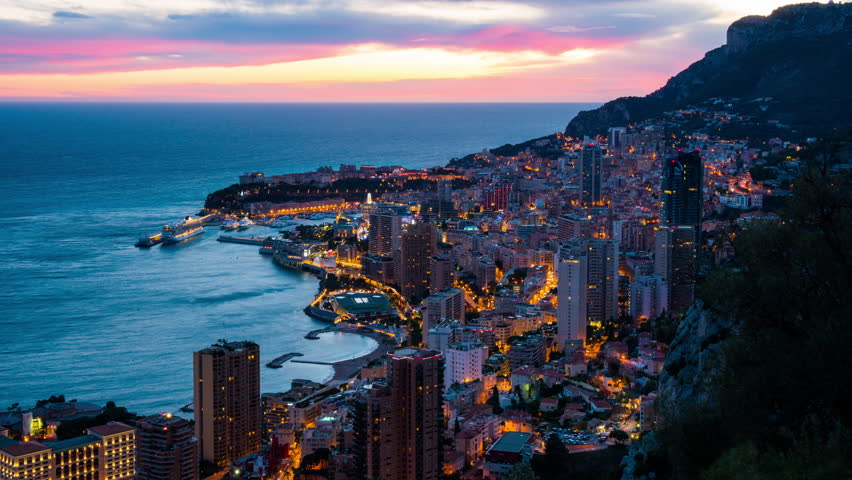 Monte Carlo, Monaco: urbanscape with city and marina in the evening. Panoramic view on Monte-Carlo from evening to night time lapse.