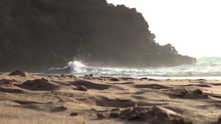 Arena de playa con olas al fondo