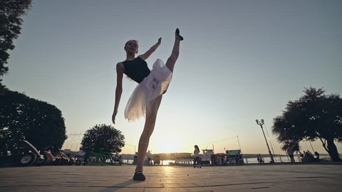 Silhouette of ballerina in ballet tutu and pointe on dramatic sky background. Young beautiful woman practicing stretching and exercises. Girl in static posture.