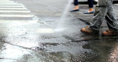 Cleaning city streets with water hose. Street sweeper cleaning asphalt in 4K