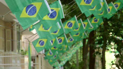 Brazil residential street flags bunting hung up for party celebration - focus pull