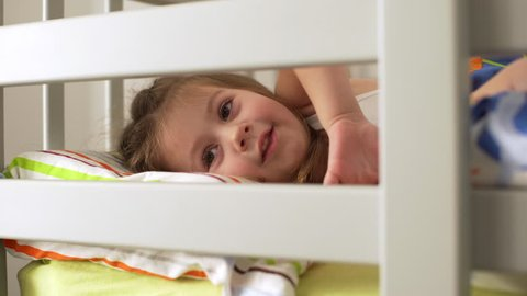 Portrait of adorable little girl having fun and fooling around, while lying in bunk bed in bedroom after awakening