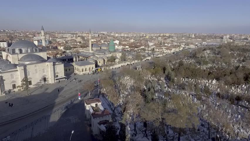 Aerial drone shot over Mevlana Rumi tomb mosque dergah green dome domes city snow cars streets people traffic grave yard highway old town Karatay, Konya
