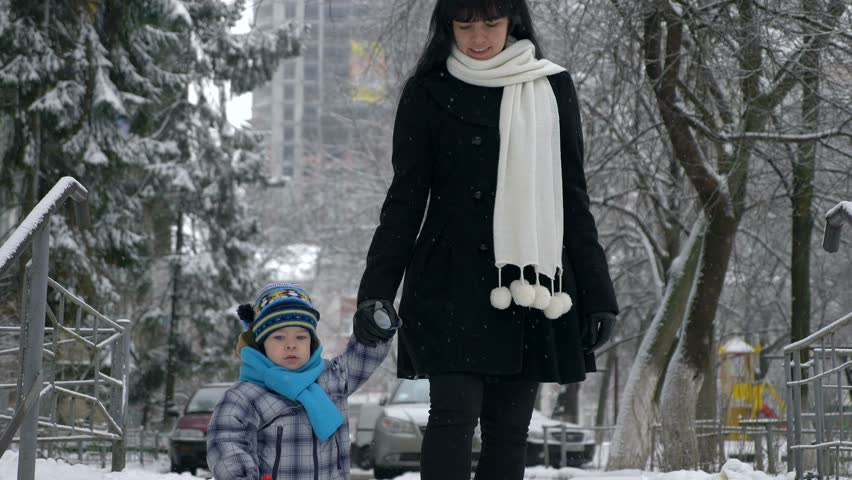 Happy Smiling Mother Walks With Child Down Stairs. Snow covered. Snow falling Slow Motion