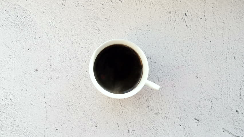 Serving coffee on a white cup. A cup of coffee on a white table, view from the top.