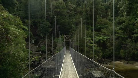 Hiker's perspective POV walking across suspension bridge in Abel Tasman National Park near shore and waterfall in tropical forest representing the beginning  of a journey and an adventure