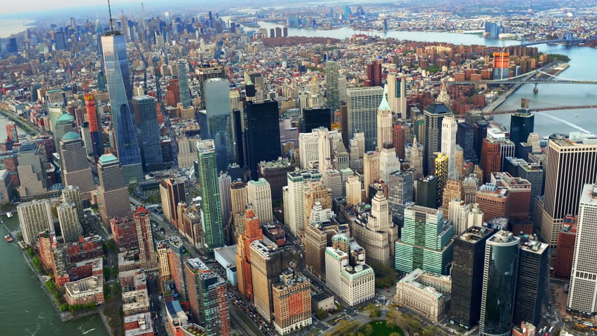 Aerial view of skyscrapers in Lower and Midtown Manhattan. Brooklyn and Manhattan Bridge in the background. Shot from a helicopter.