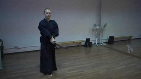 Master Kendo Swings by Katan's Sword, Trains Makes Kata in the Sports Hall with Mirrors