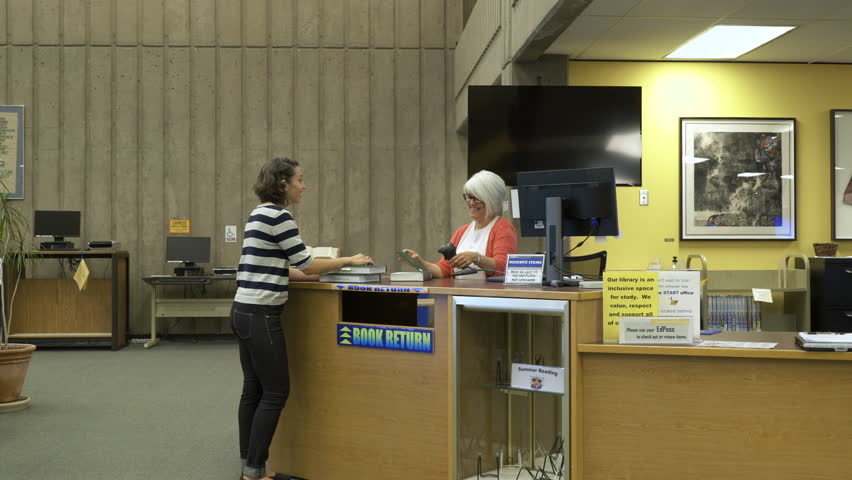 Students returning books to librarian in college library