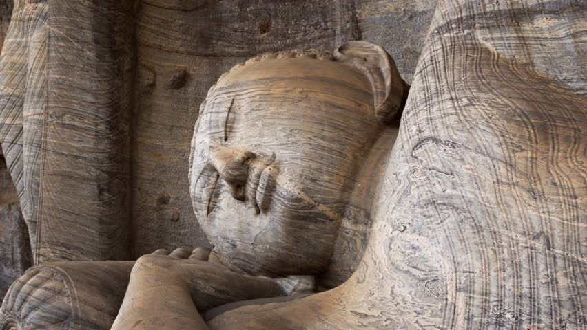 Ancient. stone Buddha sculpture at Gal Vihara. reclining on its side with a pillow. an important religious site in Polonnaruwa. Sri Lanka. 4k video
