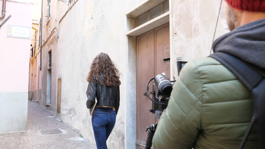 Model walking down alley way in Europe being filmed by a videoographer/Model being filmed and photographed in Italy/Noli, December 29 2017