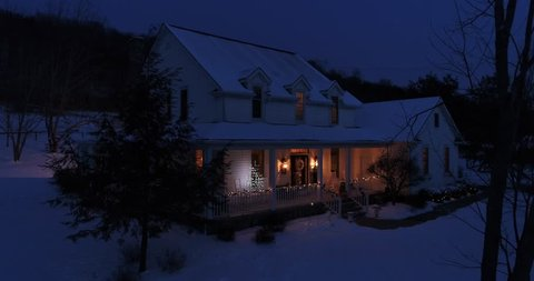 A slow aerial push into a Pennsylvanian farmhouse decorated for Christmas at night. Pittsburgh suburbs.