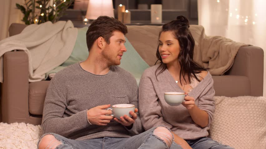 hygge, leisure and people - happy couple drinking cacao with marshmallow at home