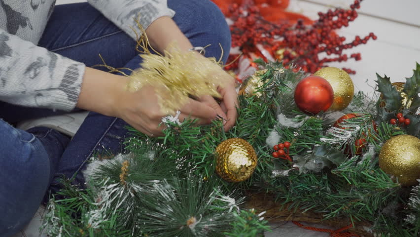 Close up of female designer who is striking Christmas wreath after celebration. Young woman is taking golden flower and ball away from green branches by her hands. Professional in blue jeans is