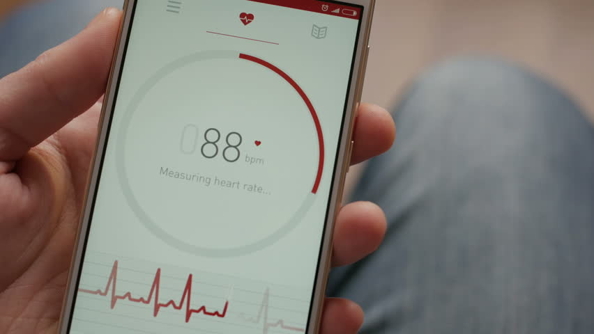 Man Looking At Health Monitoring App On Smartphone. Monitoring the heart pulse with a health application on smartphone.