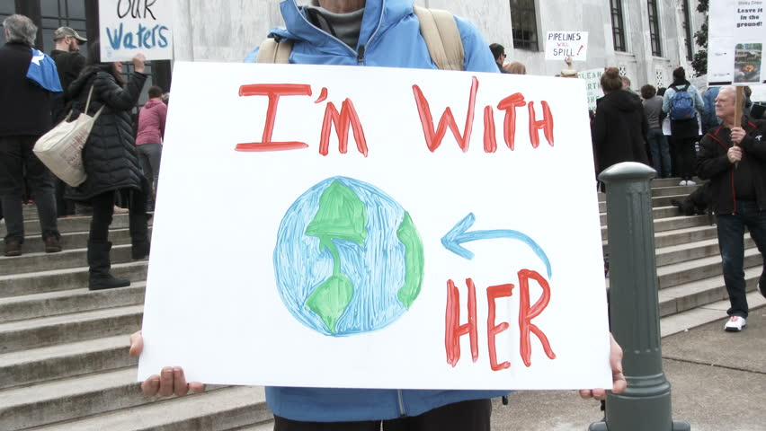 "SALEM, OREGON - FEBRUARY 2018: Woman holding sign at state capitol rally reading ""I'm With Her"" in support of clean energy and to fight global warming."