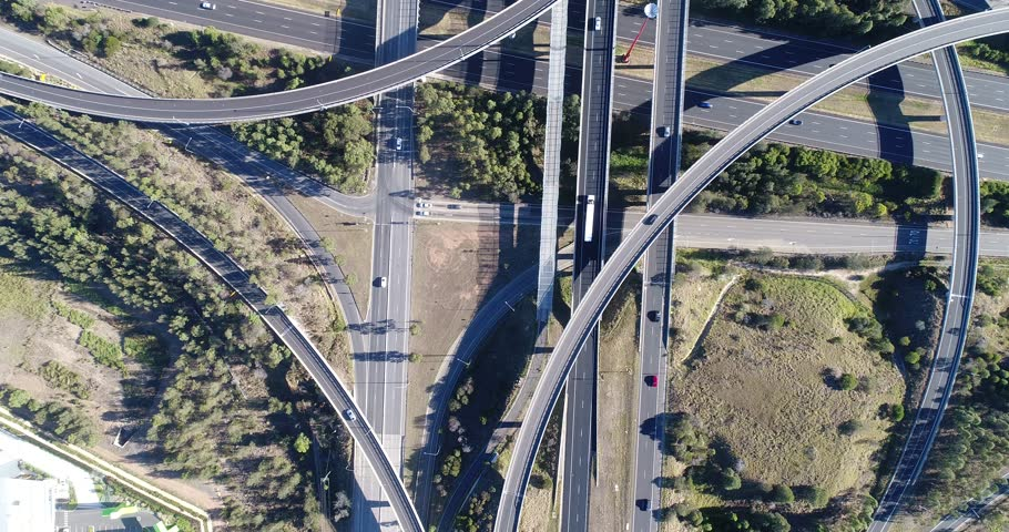 Motorways M4 and M7 Light Horse interchange in Sydney West – aerial top down flying above complex multi-level intersection.