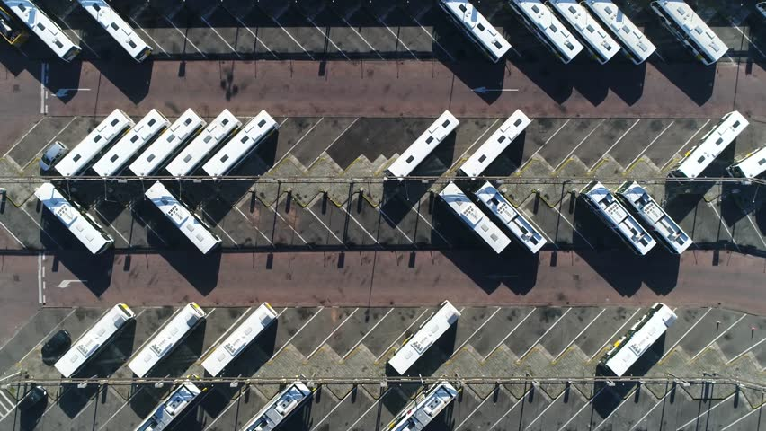 Aerial top down view of bus terminus is designated place where bus or coach starts or ends its scheduled route termini can be located at bus stations interchanges garages or bus stops 4k quality