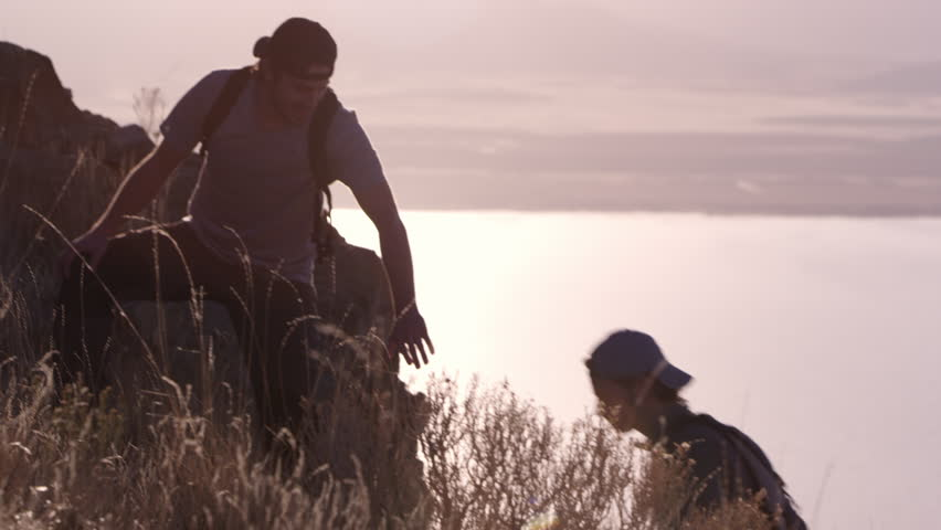 Man helping others up steep mountain path as they reach for his hand and he pulls them up the hill. | Shutterstock HD Video #1007420158