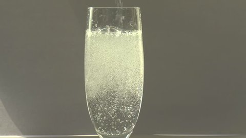 Champagne glass filling with sparkling water, white background, sun reflections