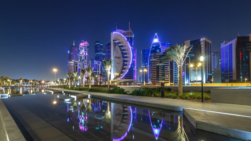 The skyline of Doha by night with starry sky seen from Park timelapse hyperlapse, Qatar. Illuminated skyscrapers and towers reflected in water of fountain