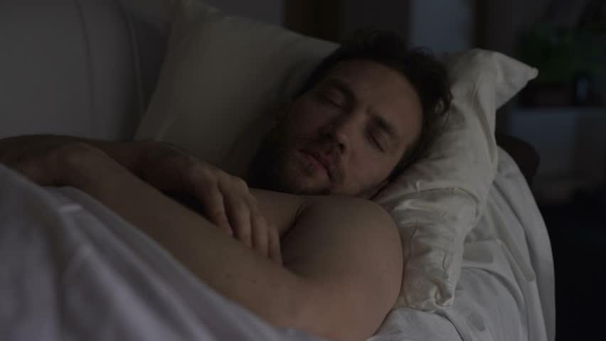 Drunken man sleeping on couch dreaming something bad, having hiccups in sleep