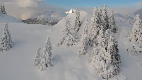 Flying over a hill with pine trees and after that opens a beautiful snow covered mountain landscape with cute chalets and high mountains in the back.