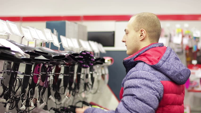 Guy choosing a hair dryer in a home appliance store | Shutterstock HD Video #1007467828