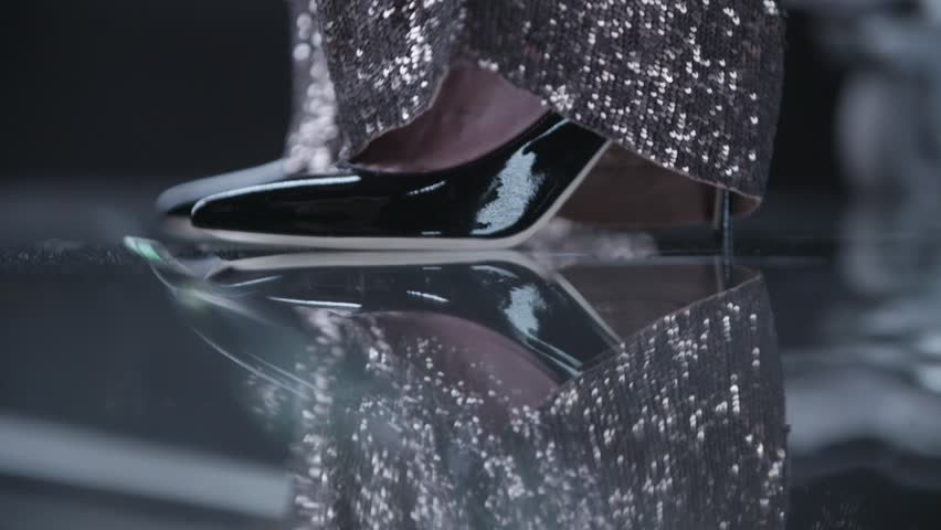 Gold shiny sparkling trousers and black elegant classy high heels.