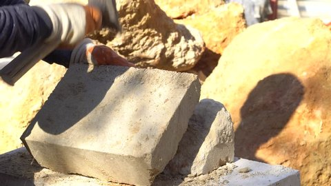 Stonemason cutting a block of granite with sledgehammer. Pitching stones for construction. Stone worker with Sledge hammer hitting concrete block. turkey Sculptor Carving Stone.