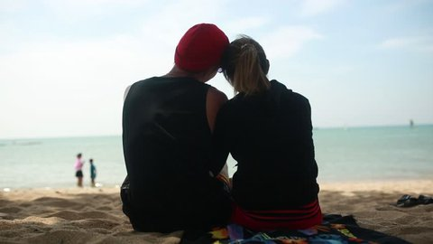 Couple lover siting watch sunset on sea beach. Video. Happy Loving couple on a tropical beach against the sea Similan Island. Young romantic couple sitting on the beach and hugging.