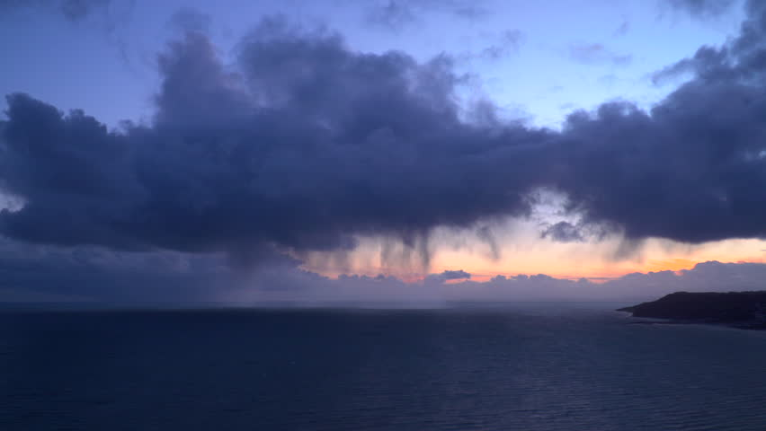 Timelapse view of sunset stormy clouds, sun and sea rushing towards camera