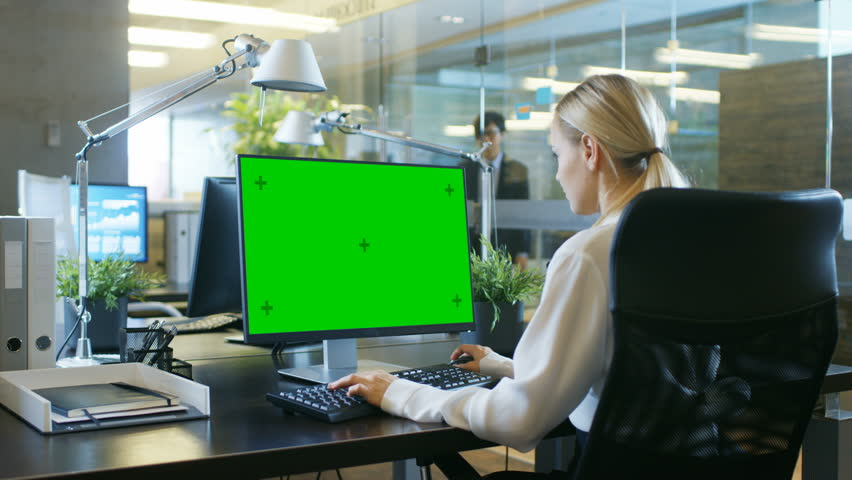 In the Office Businesswoman works at Her Desk on a Personal Computer with Mock-up Green Screen. Colleague Enters Office and Takes Place at His Desk. Shot on RED EPIC-W 8K Helium Cinema Camera. | Shutterstock HD Video #1007506432